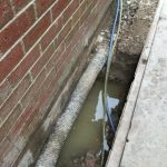 Water ingress into sub-floor void caused by high water table, impermeable sub-soils and defective drainage. In this case the existing land drain has been installed by others many years ago at the incorrect height rendering it ineffective.